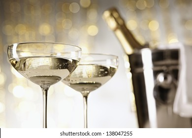 Two glasses of champagne, bottle and cooler in the background, selective focus