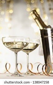 Two glasses of champagne with bottle in cooler in the background, selective focus