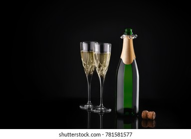 Two glasses of champagne with the bottle, glitter, on a black background. Night of celebration concept.