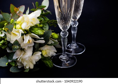 Two glasses of champagne and  bouquet of white flowers on black