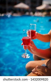 two glasses of champagne by the pool in the hands of the newlyweds