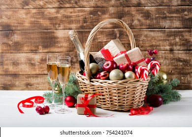 Two glasses of champagne with christmas basket with bottle, gifts with red satin ribbon, candy canes, pine cones, golden garlands on dark brown wooden background, new year celebration concept