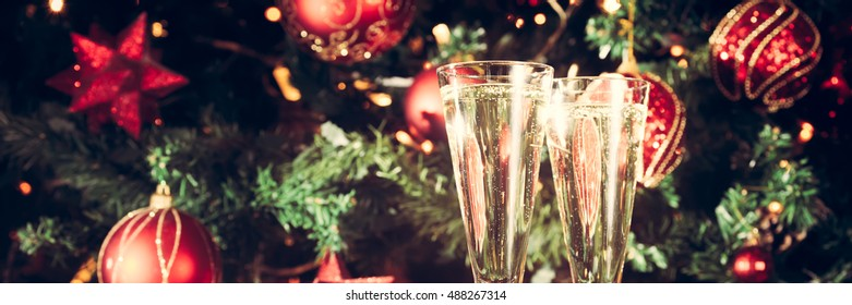 Two glasses of champagne with Christmas tree background. Holiday season background. Traditional red and green Christmas decoration with lights. Holiday party. Horizontal, cover or banner size