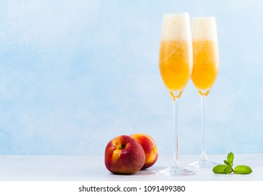 two glasses of champagne with a cocktail of Bellini and fresh peaches on a blue background. summer refreshing drink
