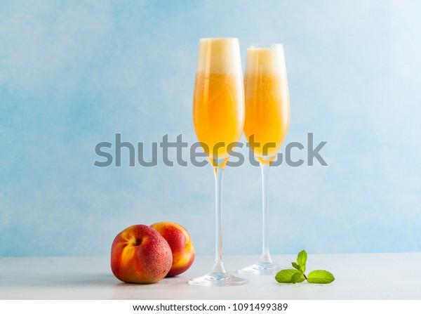 deux verres de champagne avec un cocktail de Bellini et des pêches fraîches sur fond bleu. boisson rafraîchissante d'été