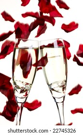 Two glasses of champagne with diamonds with falling rose petals in background