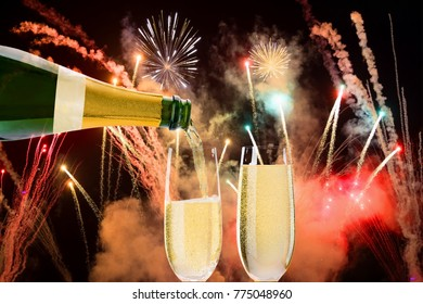 Two glasses of champagne filled with fireworks in the background.
