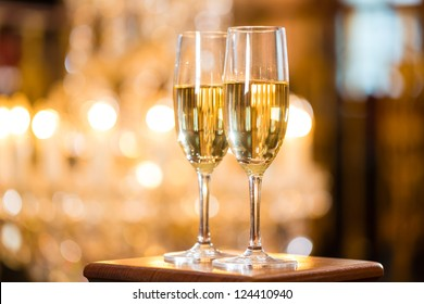Two glasses of champagne in a fine dining restaurant, a large chandelier is in Background