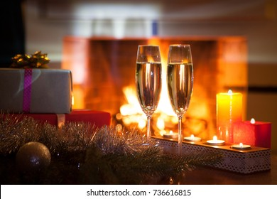 Two glasses with champagne in front of the fireplace. New Year. Christmas.