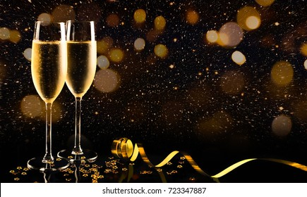 Two glasses of champagne with golden confetti, glitter, serpentine and lights. Night of celebration concept