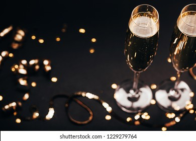 Two glasses of champagne with golden decoration on black elegant background. Top view, place for text. Festive concept.