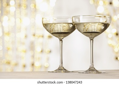 Two glasses of champagne infront of gold reflecting background, selective focus