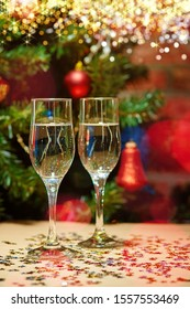 Two glasses of champagne on the background of a beautifully decorated balls, garlands, stars Christmas tree. Around the glow of rays and bokeh lights