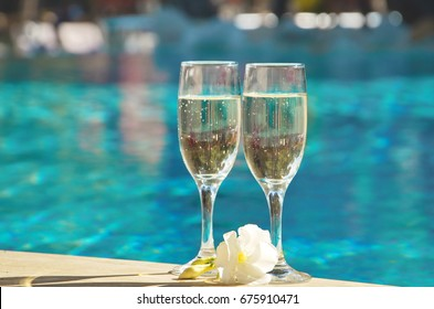 Two glasses of champagne on the background of the pool