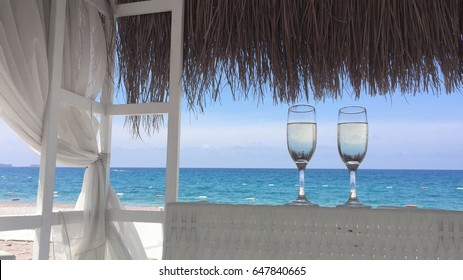 Two glasses of champagne on the beach with white sand on the terrace