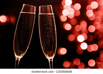 Two glasses of champagne on black stylish background with bokeh circles. Place for text. Festive concept. Living Coral - Color of the Year 2019.