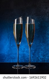 Two glasses with champagne on a black mirror surface. Blue background Concrete wall. Black glass. Crystal glass