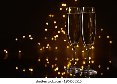 Two glasses of champagne on a dark background with LED lights garland. Copy space for text.