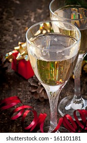 Two glasses of champagne on a dark old wooden background
