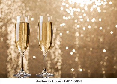 Two Glasses of Champagne on a golden garland background. Night Party life concept. - Image