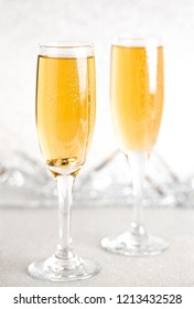 Two Glasses of Champagne on a Silver Glitter Backdrop