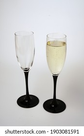 Two glasses of champagne on a white background. One glass is empty and the other is full.