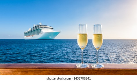 Two glasses of champagne on wooden railing at sunset. Blurred cruise ship in the background. Luxury travel vacation.