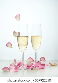 two glasses of champagne, pink ribbon and falling rose petals