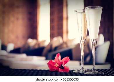 Two glasses of champagne with red flower in a spa lounge. Spa time concept. Spa lounge area. Valentines background. Romance concept. Horizontal, tone filter applied