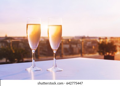 two glasses of champagne at rooftop restaurant with view of city skyline, luxury romantic dinner for couple