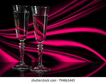 Two glasses of champagne stand on a mirror surface. Two glasses of champagne on a background of fabric with folds. Glasses with alcoholic drinks on a background of blurred fabric. Champagne.