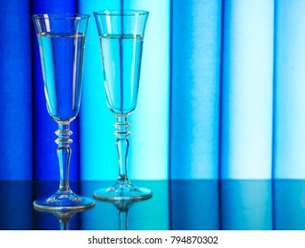 Two glasses of champagne stand on a mirror surface. Two glasses of champagne on a background of blue fabric. Glasses with alcoholic drinks stand against the background of a blurred blue fabric.