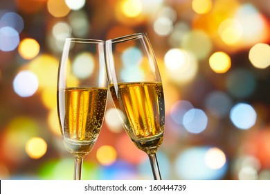 two glasses of champagne toasting against bokeh lights background