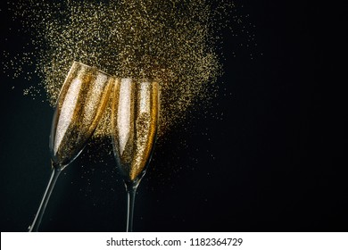 Two glasses of champagne toasting with golden glitter  on a dark background. Flat lay. Night of celebration concept