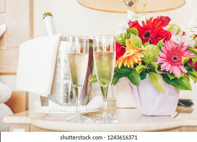 Two glasses of champagne in the upscale hotel room. Dating, romance, honeymoon, valentine, getaway concepts. Horizontal. Light warm toning