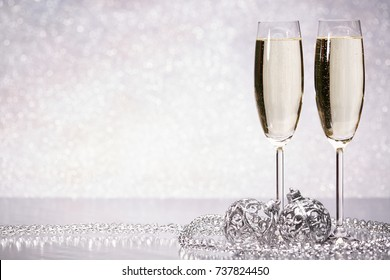 Two glasses with champange and christmas decorations on a silvery background. New year and Christmas.