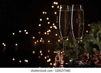 Two glasses with champange, fir tree branch and gingerbread cookies on a dark background with LED lights garland. New year and Christmas.