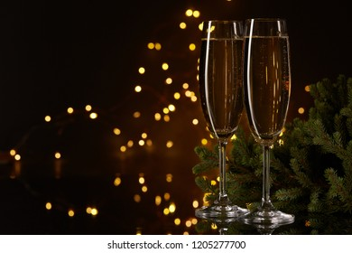 Two glasses with champange and fir tree on a dark background with LED lights garland. New year and Christmas.