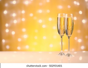 Two glasses with champange, gift boxes on a yellow background with lights of garland.