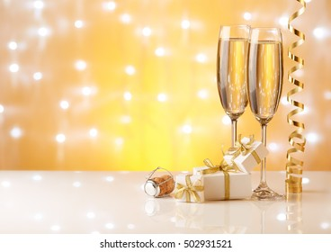 Two glasses with champange, gift boxes and christmas decorations on a yellow background with lights of garland.  New year and Christmas.