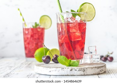 Two glasses of cherry mojito garnished with lime slices