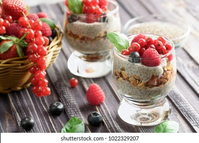 Two glasses of chia pudding with fresh strawberries, raspberries and blueberries. Basket with berries. On a wooden grey background.