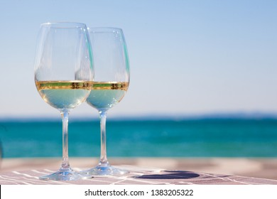 two glasses of chilled white wine on table over Garla Lake backgound