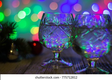 Two glasses of christmas champagne with christmas tree decorated of red and silver balls against light bokeh background.