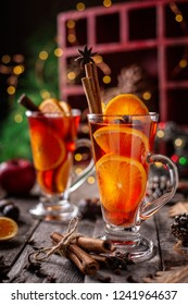 Two Glasses of Christmas mulled red wine with spices and fruits on a wooden rustic table. Vertical composition