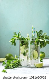 Two glasses of classic mojito cocktail with fresh mint, limes, crushed ice, retro cocktail tubes with ingredients above. Pin up style, sunlight, green background.