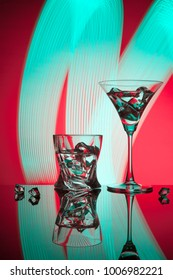 Two glasses a cocktail Martini whisky ice, against the red background of beautiful light effects.
