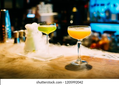Two Glasses of Cocktails with Steam, Ice and Amazing Blurred Background in the Luxury Bar