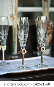 Two glasses of cold champagne .Two wedding glasses of groom and bride on the table