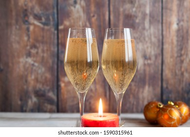 Two glasses of cold white champagne or cava sparkling wine  for Christmas days with Christmas decoration and burning candle on wooden table and wood background